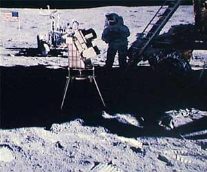 """Фото NASA AS16-114-18439. Камера для съемок неба в ультафиолетовых лучах. На заднем плане - астронавт Чарльз Дьюк, """"луномобиль"""" и флаг."""